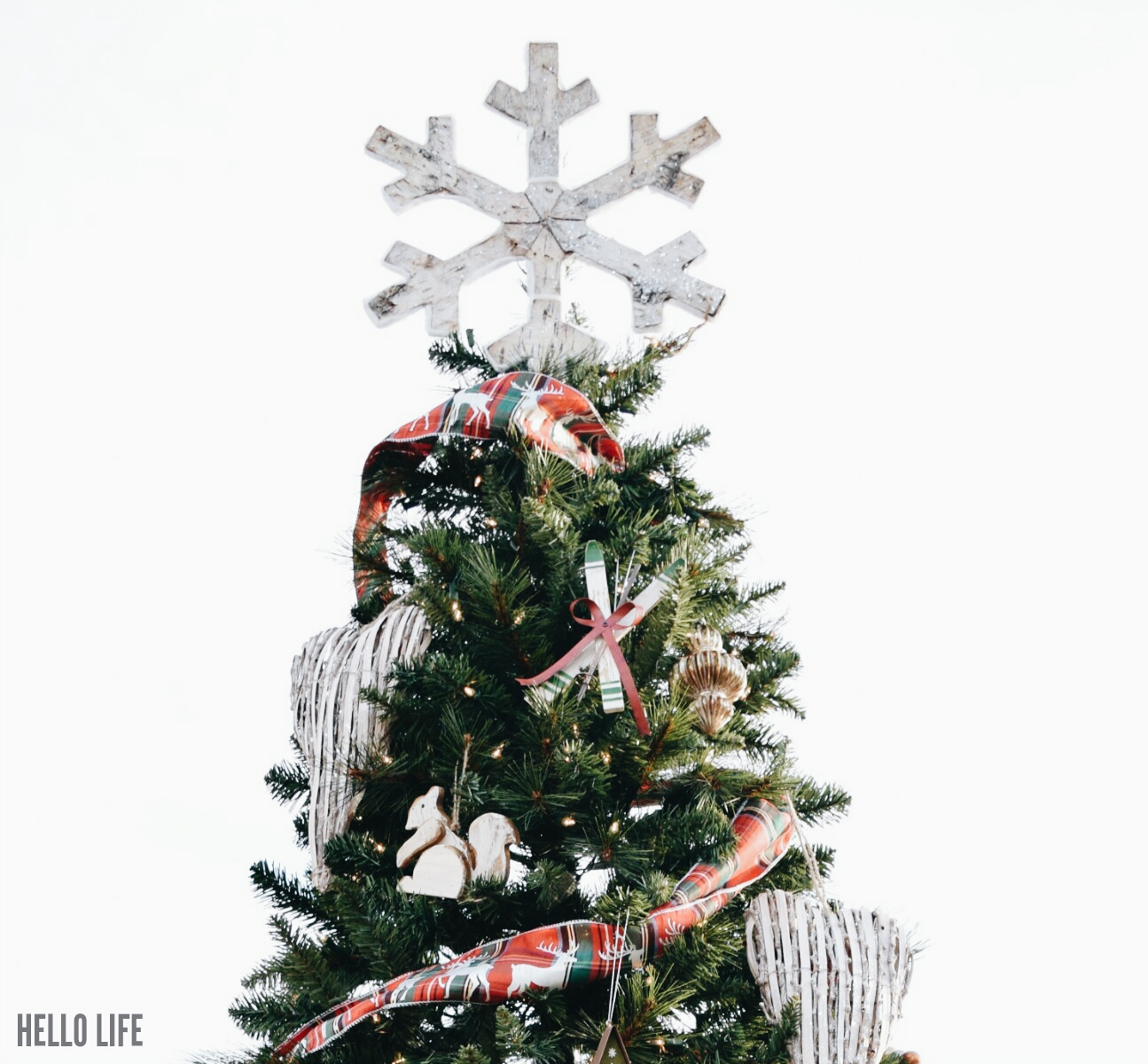 A beautiful rustic snowflake tops this gorgeous outdoor Christmas tree! #michaelsmakers